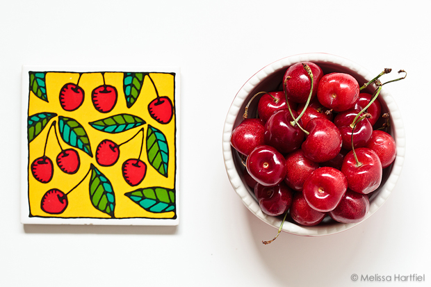 a bowl of cherries next to a coaster with painted cherries on it.