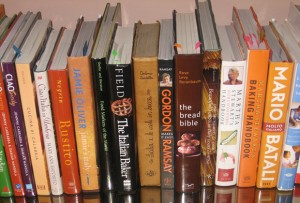 A shelf crammed with cookbooks