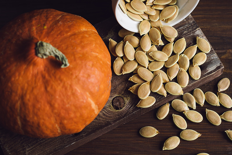 Bowl with dried pumpkin seeds and a pumpkin