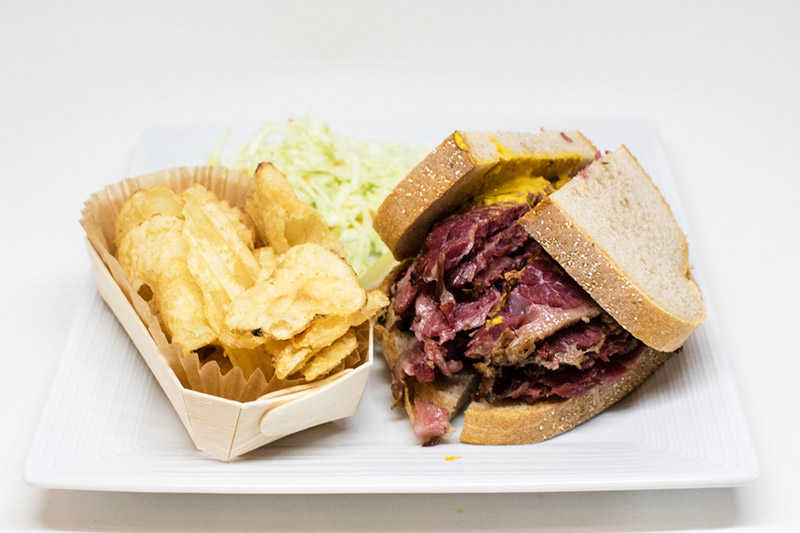 smoked meat sandwich and potato chips
