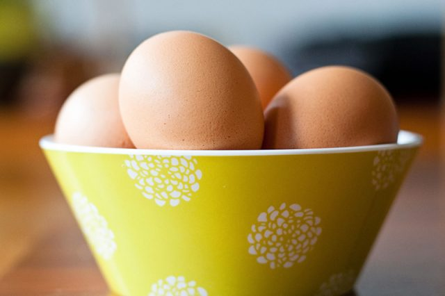 An olive green bowl of brown eggs
