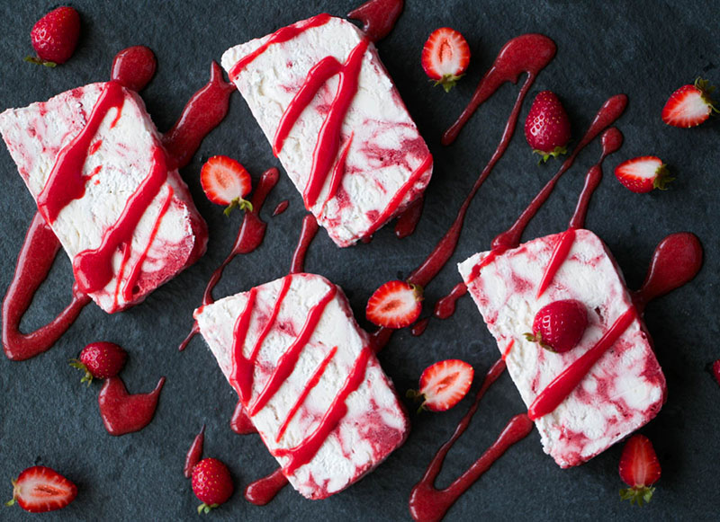 Sliced Strawberry Rosewater Semifreddo drizzled with strawberry puree.