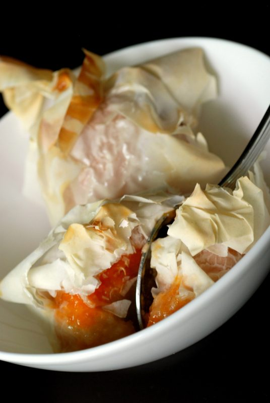 A bowl of apricot parcels with honey glaze and a spoon