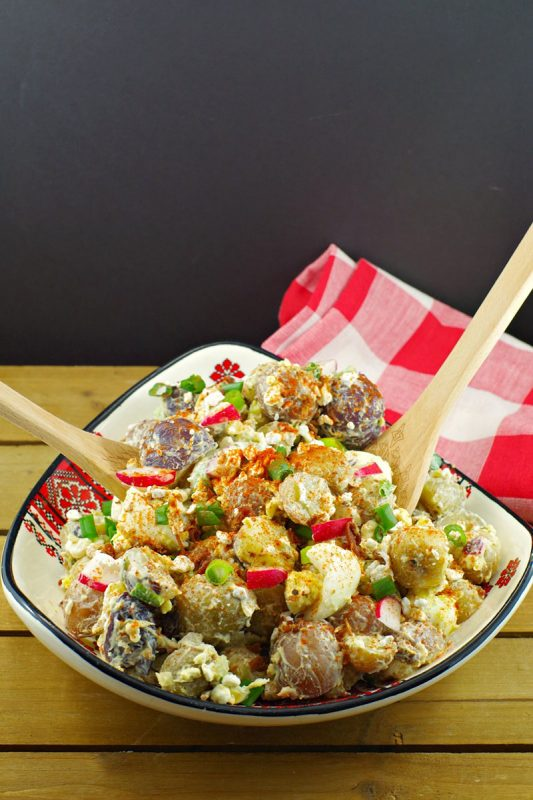 Perogy Potato Salad in a bold with serving tongs