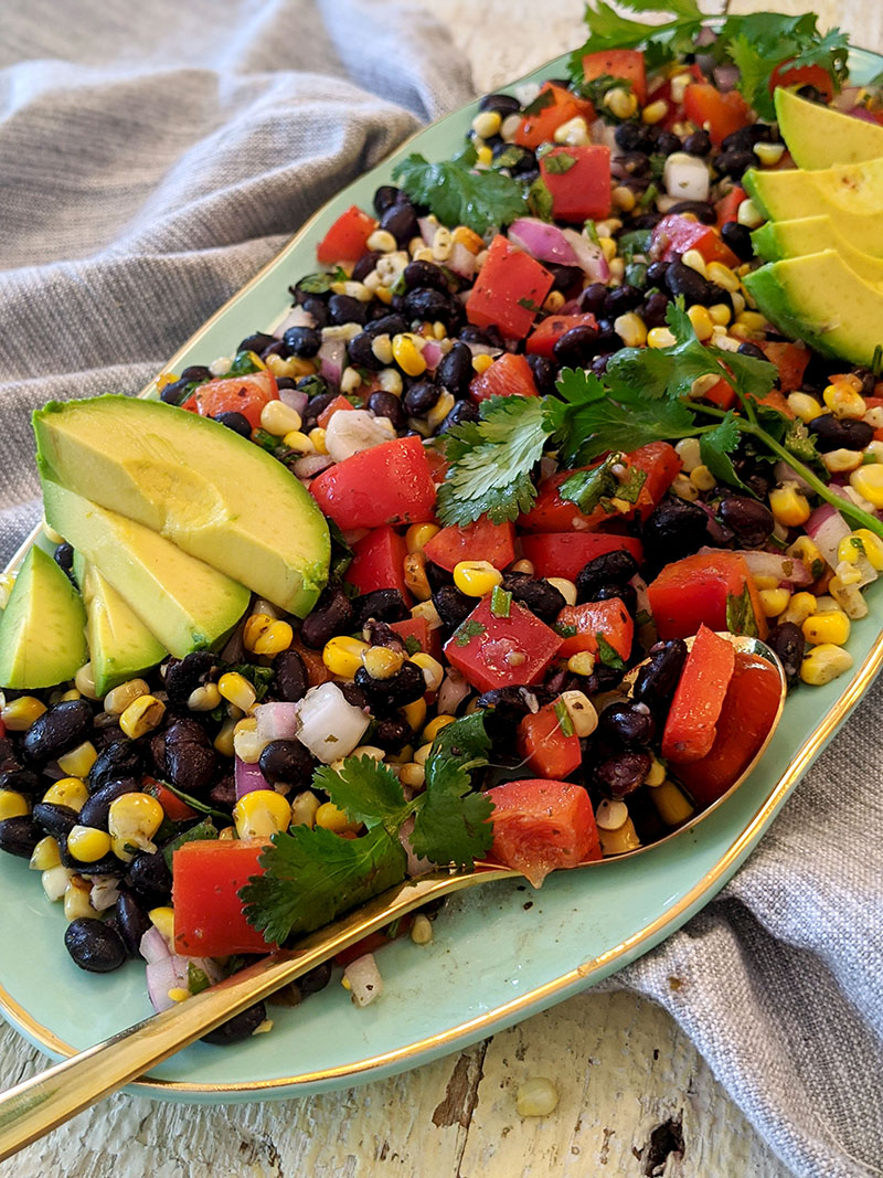 Charred corn salad with cilantro dressing and sliced avocado on a serving platter