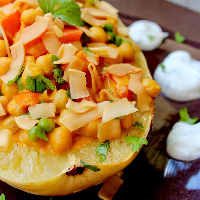 """A spaghetti squash """"bowl"""" with chickpeas in red curry sauce."""