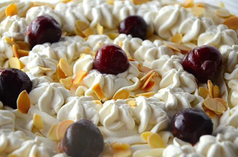 the top of a trifle covered with whip cream and cherries