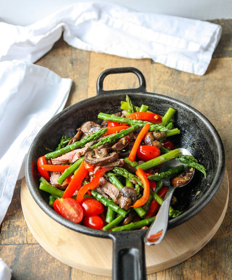 A cast iron skillet with a colorful beef and vegetable stir fry