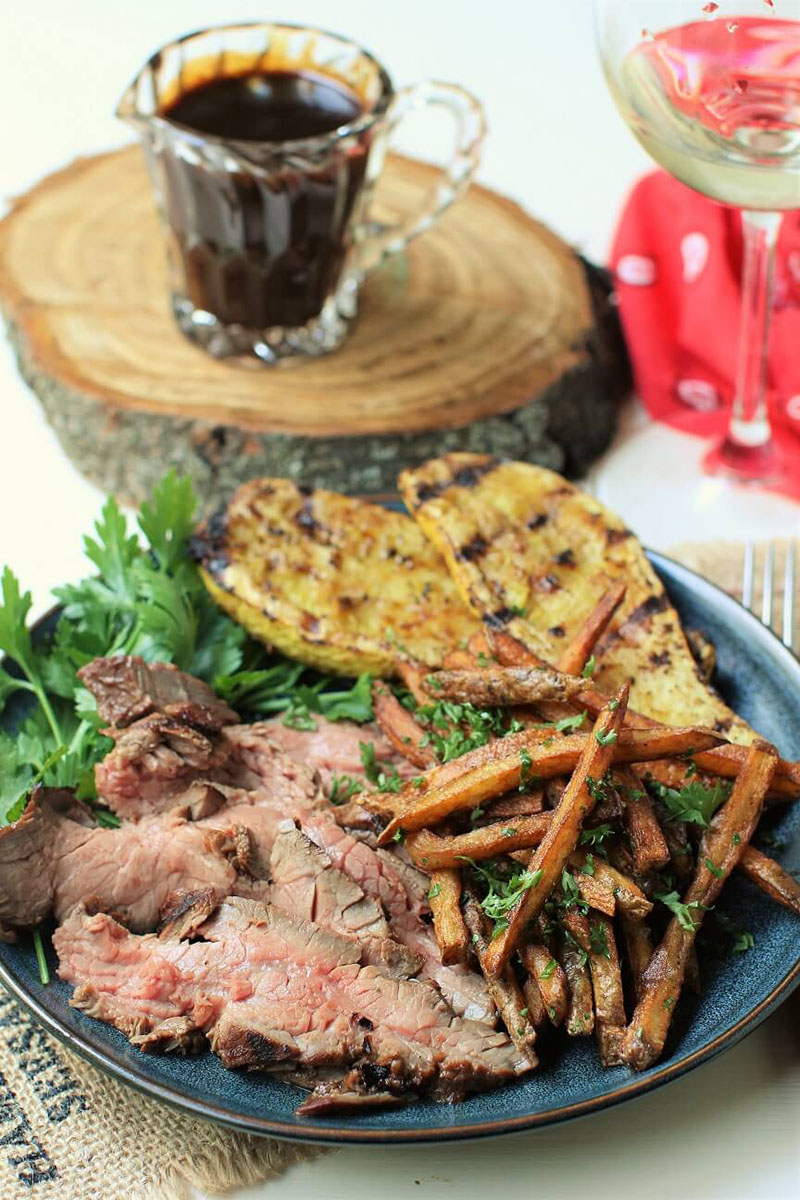 A plate of grilled flank steak with sweet potato fries and greens