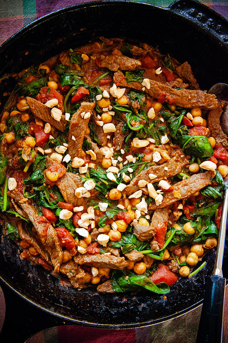 A skillet full of colourful chickpea beef curry with spinach and tomatoes