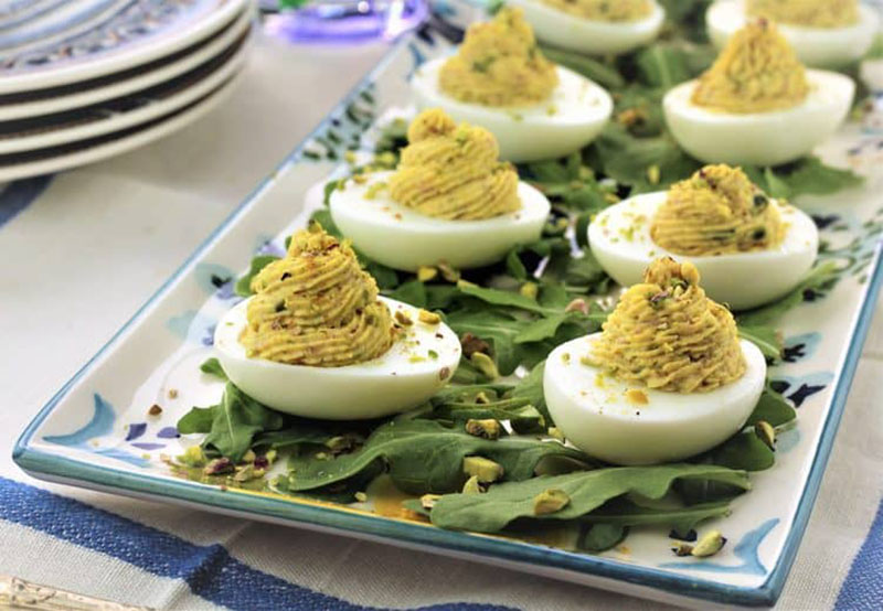 a platter of mortadella, ricotta and pistachio deviled eggs.